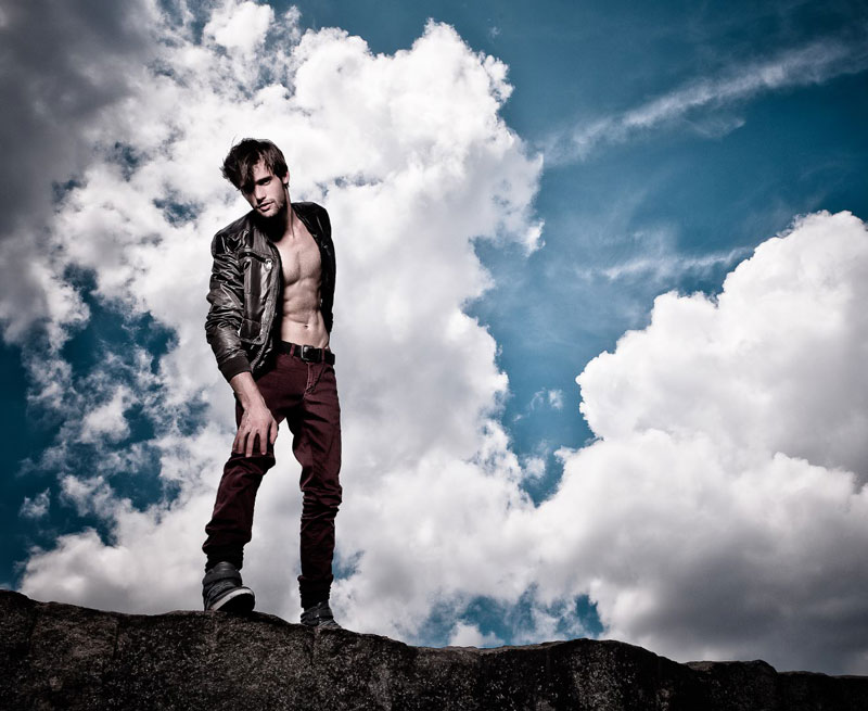 Alex Lago - model - Alex standing on a rock with a blue, cloudy sky behind him